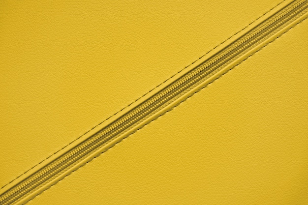 Yellow plastic zipper on leather material. clothes and accessories background. diagonal zipper.