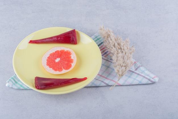Piatto giallo di polpe di frutta secca e pompelmo sul tavolo di pietra.