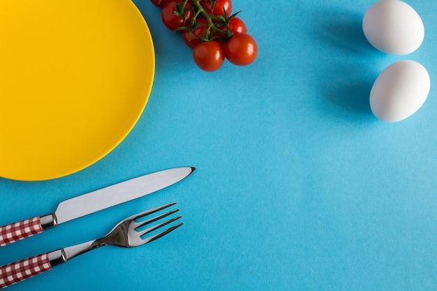 黄色のプレート、フォーク、ナイフ、青い背景の朝食の材料。上面図。