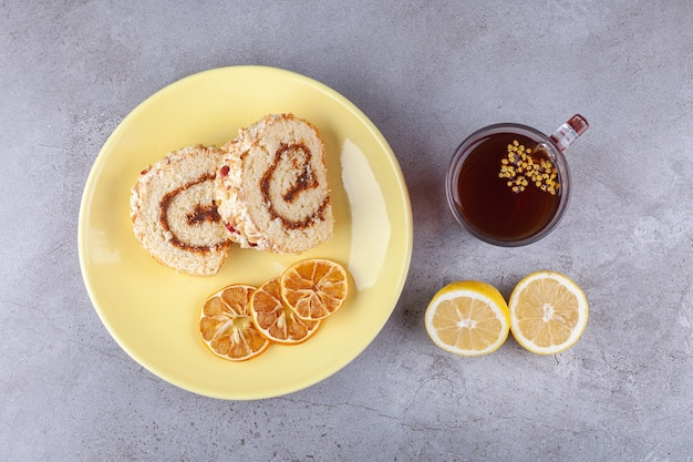Yellow plate with sliced roll cake and cup of tea on stone surface.