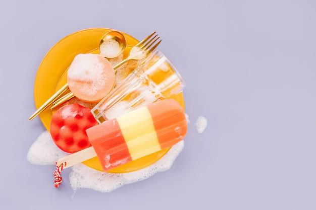 비누 거품 배경에 숟가락, 포크, 스폰지가 있는 노란색 접시. 설거지 개념입니다. 평면 위치, 상위 뷰.