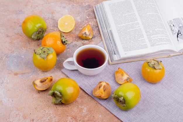 Datteri di prugne gialle e fette di limone con una tazza di tè.