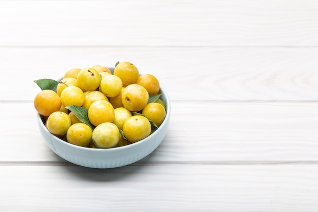 Yellow plum mirabelle fruit in bowl on white wooden table. copyspace
