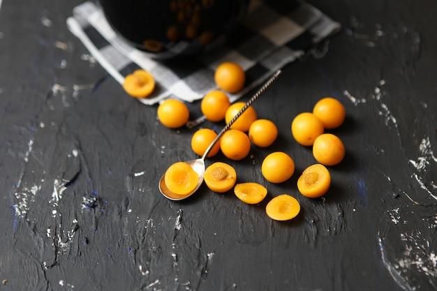 Желтые сливы на черном фоне. ингредиенты для варенья. фотография еды. осенняя концепция,