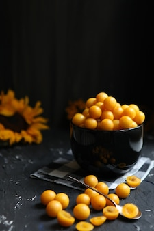 Желтые сливы на черном фоне. ингредиенты для варенья. фотография еды. вертикальное изображение. желтый подсолнух, осенняя концепция, урожай.