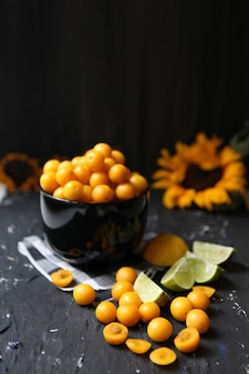 Yellow plums with lemon and lime on the black background. ingredients for a jam. food photography. vertical image. yellow sunflower, autumn concept, tasty fruits and vitamins.