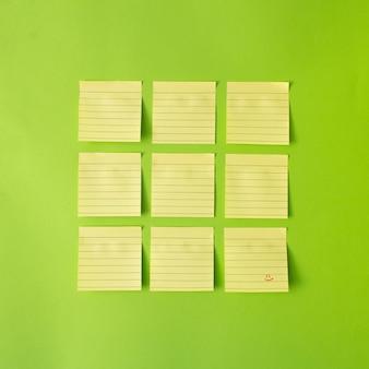 Желтые стикеры, расположенные в квадрате из девяти, с одной запиской с красной улыбкой на ней. синий фон. минимальная креативная концепция,