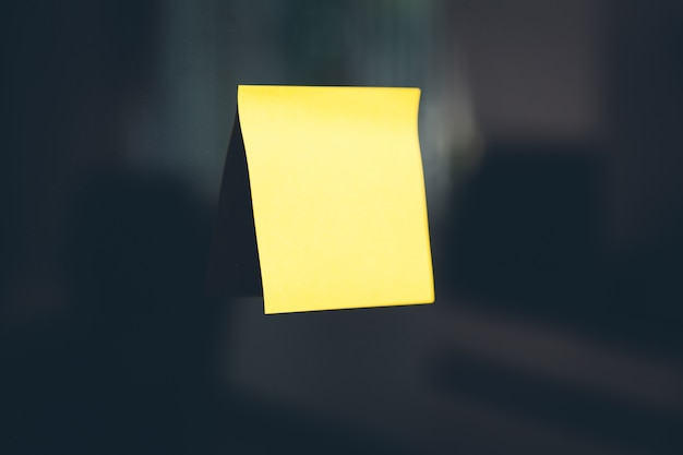 Yellow post-it stuck on a black wall