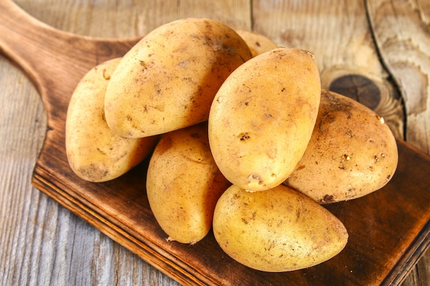 Yellow potato tubers on an old wooden table.