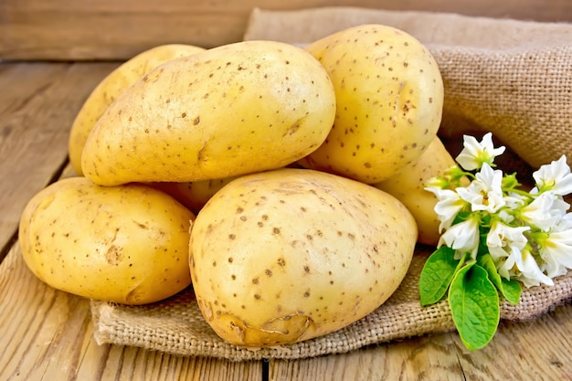 Yellow potato tubers with a flower on sacking on a wooden boards