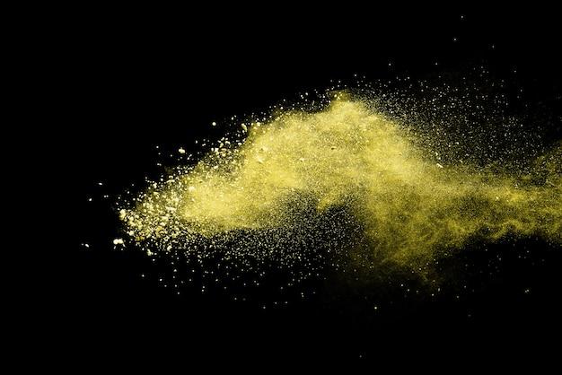 黒の背景に分離された黄色の粉塵爆発