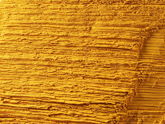 Yellow powder of grated turmeric with texture, food background. view from above.