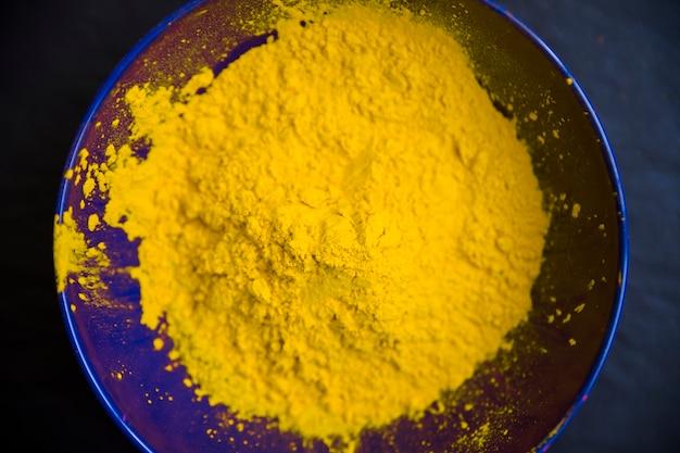 검은 배경에 파란색 그릇 안에 노란 가루