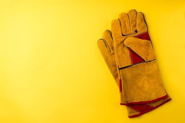 노란색 배경에 노란색 보호 건설 장갑입니다.