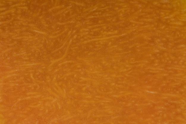 노란 호박은 펄프의 질감으로 반으로 자른다. 호박 조각 배경 가까이, 상위 뷰