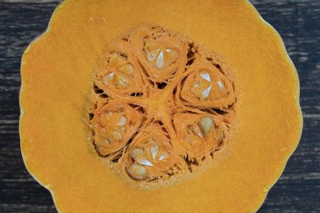 노란색 호박은 씨앗과 펄프의 질감으로 반으로 자릅니다. 호박 조각 배경 가까이, 상위 뷰
