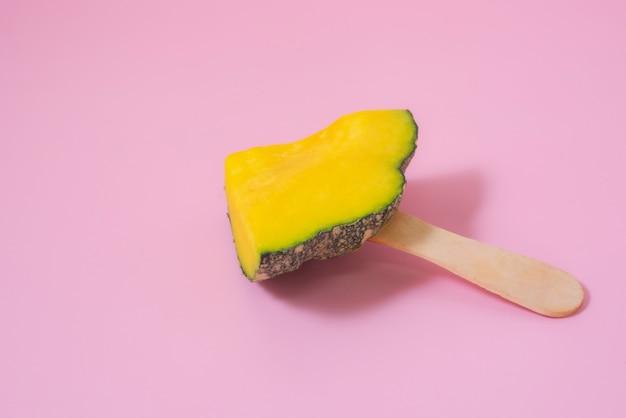 햇빛 반사가 있는 분홍색 배경에 노란색 호박 아이스크림