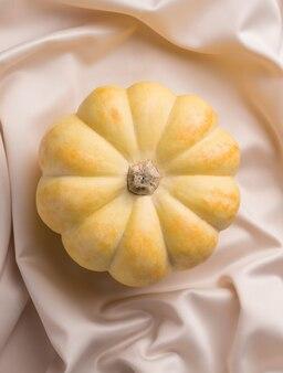 Желтая тыква на шелковой ткани. вид сверху. современный изысканный дизайн