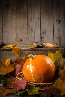 Yellow pumpkin on rustic wooden table.