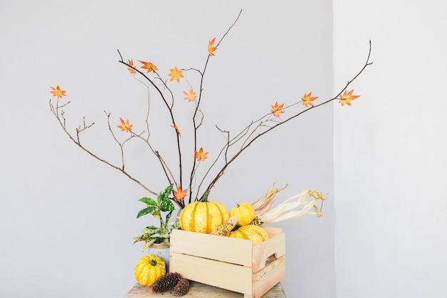 Желтые тыквы в деревянной корзине на сером фоне. интерьер комнаты