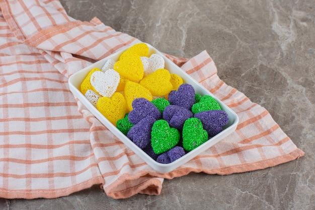 Желто-фиолетовые и зеленые конфеты. вкусные конфеты на белой тарелке.