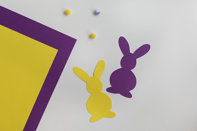 Yellow and purple colored paper, fluffy balls and patterns of easter rabbits