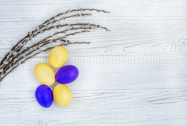 Yellow and purple easter eggs and willow twigs on a white background. concept happy easter.