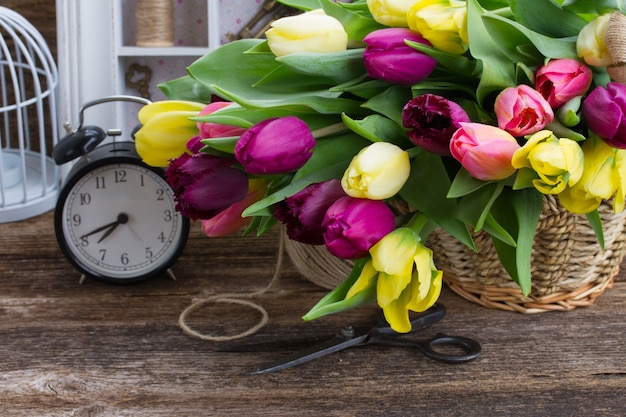 Yellow  and purple fresh tulip flowers with retro clock  on wooden table