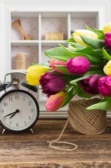 Yellow  and purple fresh tulip flowers with retro clock