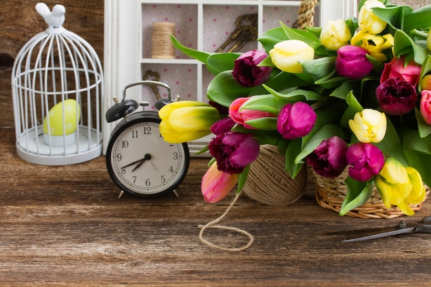 Yellow  and purple fresh tulips with retro clock  on wooden table