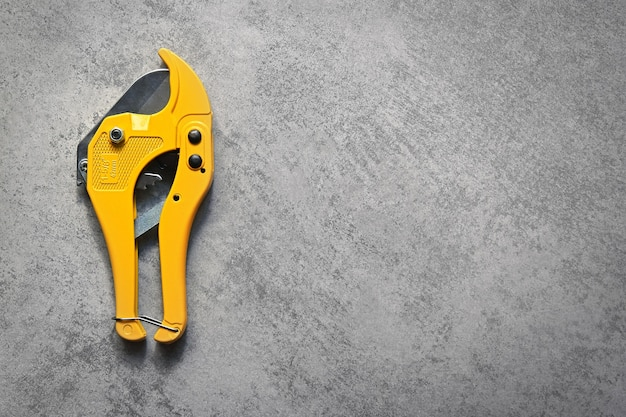 Yellow pvc pipe cutter on gray background with copy space