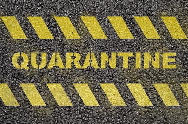 Yellow quarantine text warning on the black asphalt road surface