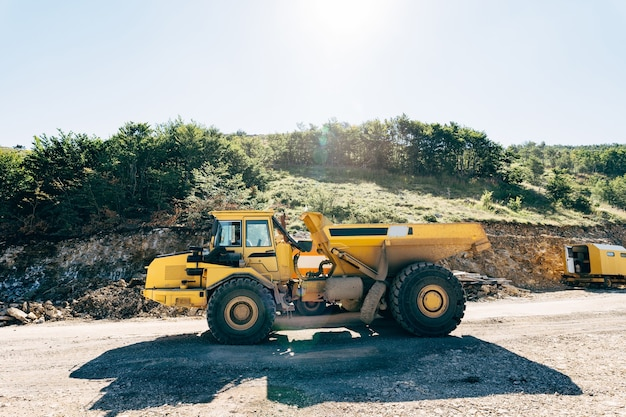 Yellow quarry dump truck driving on the road