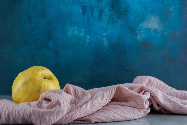 Плоды желтой айвы, изолированные на розовой скатерти.