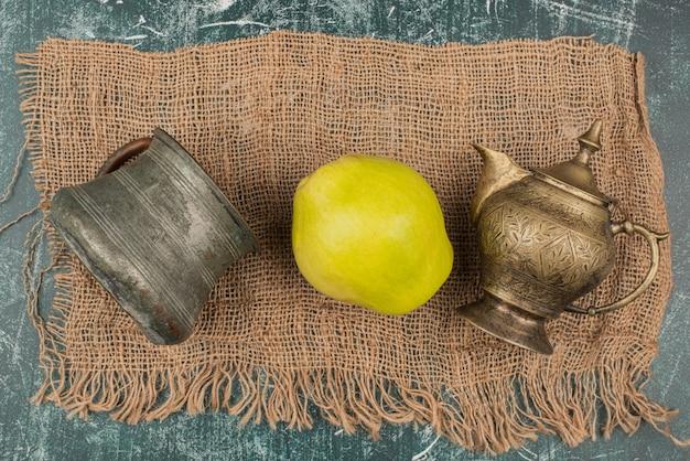 Желтая айва со старинными чашками на ткани из мешковины