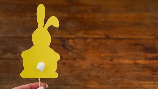 칫솔에 종이로 만든 노란 토끼. 손에는 부활절 베이킹 장식이 있습니다. 나무 배경에 부활절 카드