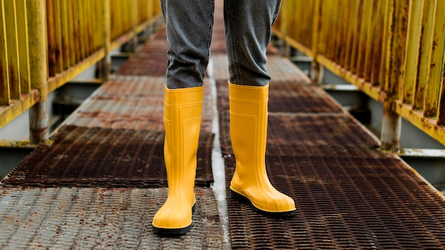 Yellow rain boots on bridge