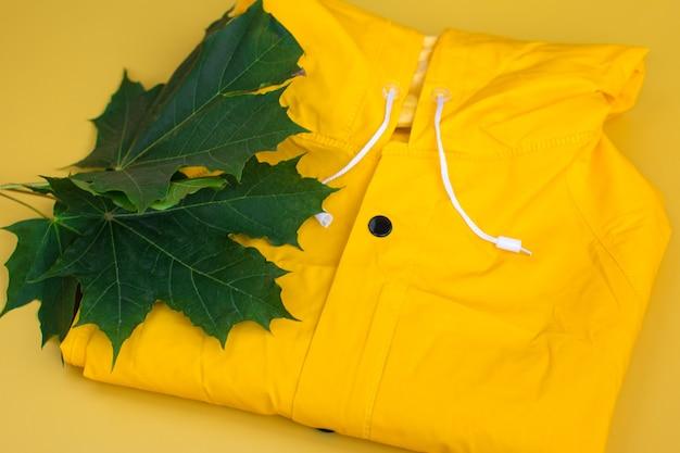 A yellow raincoat neatly folded on a shelf. autumn weather