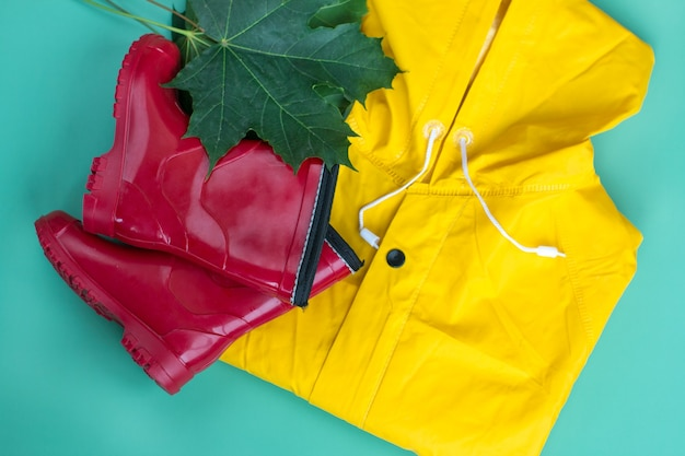 A yellow raincoat and red rubber boots. autumn maple leaves raincoat sale