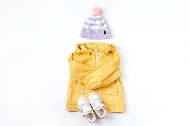 子供の帽子とスニーカーと黄色のレインコート。秋の子供服のかわいいセット。