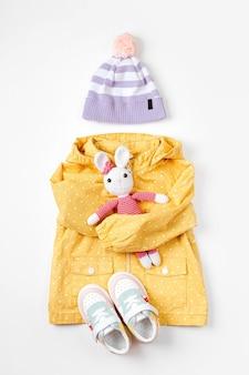 おもちゃのバニーと子供用の帽子とスニーカーが付いた黄色のレインコート。秋の子供服のかわいいセット。