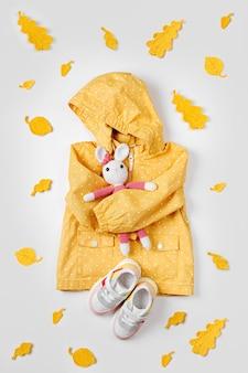 おもちゃのバニーと子供用スニーカーが付いた黄色のレインコート。秋の子供服のかわいいセット。