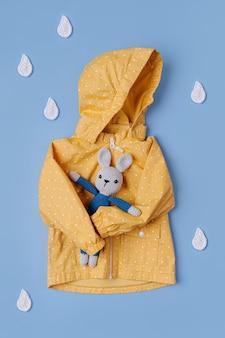 파란색 배경에 장난감 토끼와 장식용 빗방울이 있는 노란색 비옷. 가을 아동복. 가을 분위기