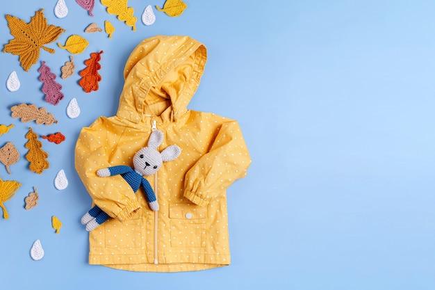 파란색 배경에 장난감 토끼와 노란색 비옷입니다. 가을 아동복. 가을 분위기