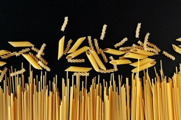 Желтые сырые домашние спагетти и макароны пенне на черной бетонной поверхности в нижней части кадра.