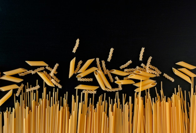 Yellow raw homemade spaghetti and penne pasta on a black concrete background
