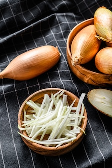 Yellow raw shallot onions, sliced and halved.