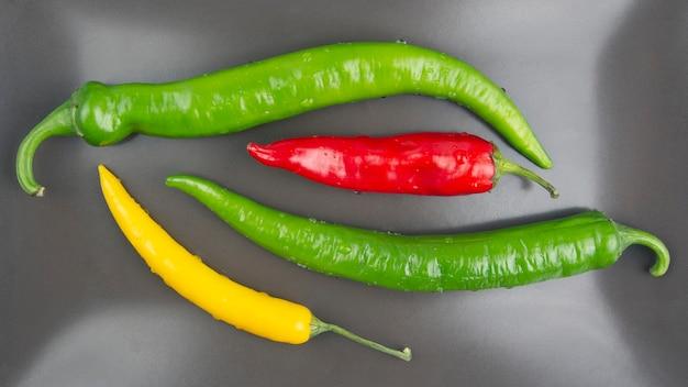 Желтый, красный и зеленый острый перец чили на тарелке. перец. растительное витаминное питание.