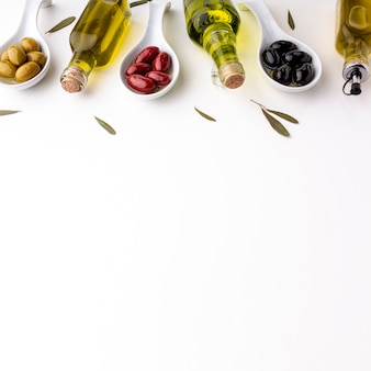 Yellow red black olives in spoons  with leaves and oil bottles with copy space