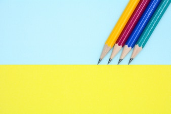 Yellow, red, blue, and green pencil on blue and yellow paper - background